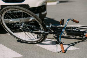 broken bicycle in front of car